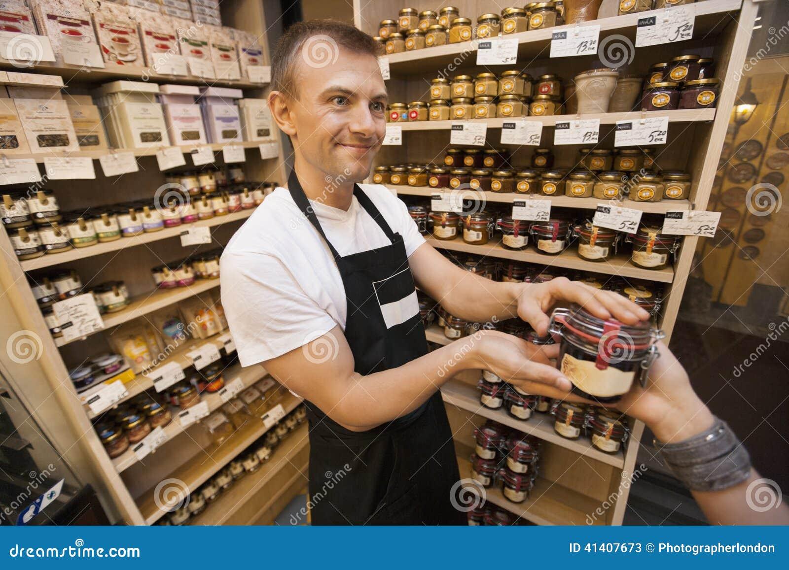 给瓶子果酱的推销员女性顾客在杂货店