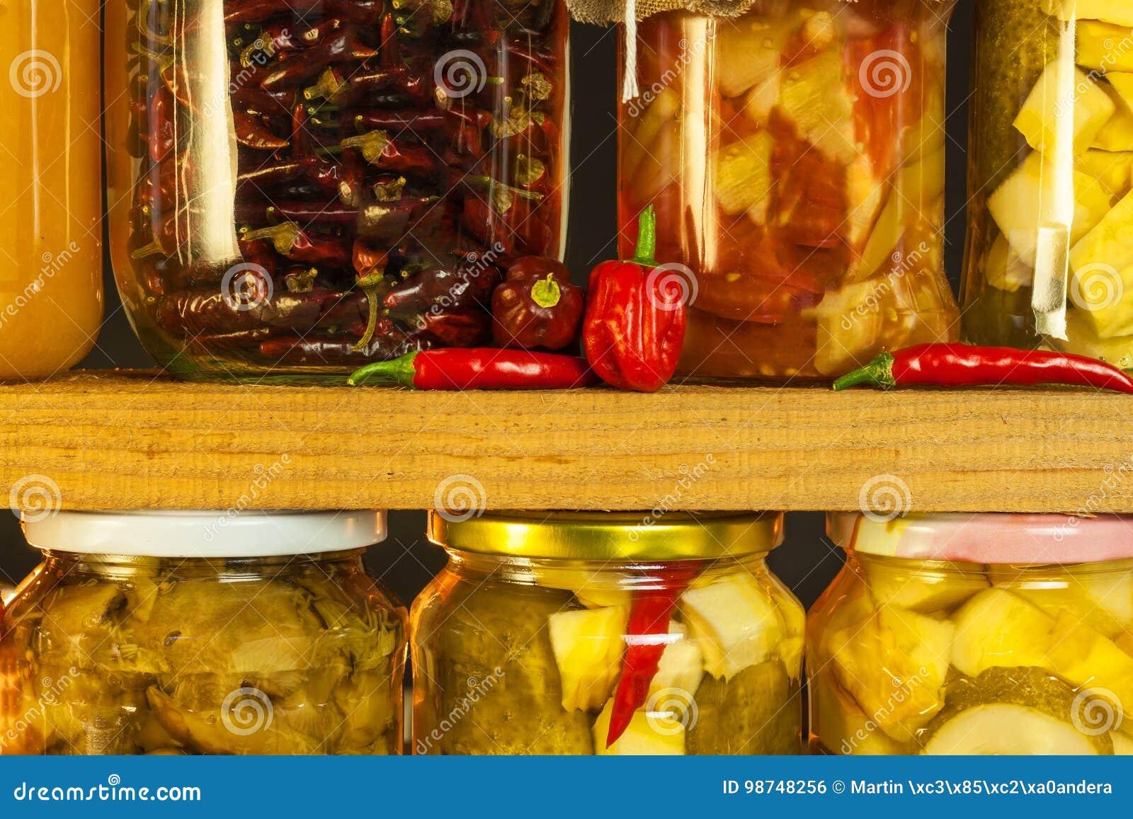 瓶子用用卤汁泡的食物和有机未加工的蔬菜 在木背景的被保存的菜 各种各样的用卤汁泡的食物 在a的生活
