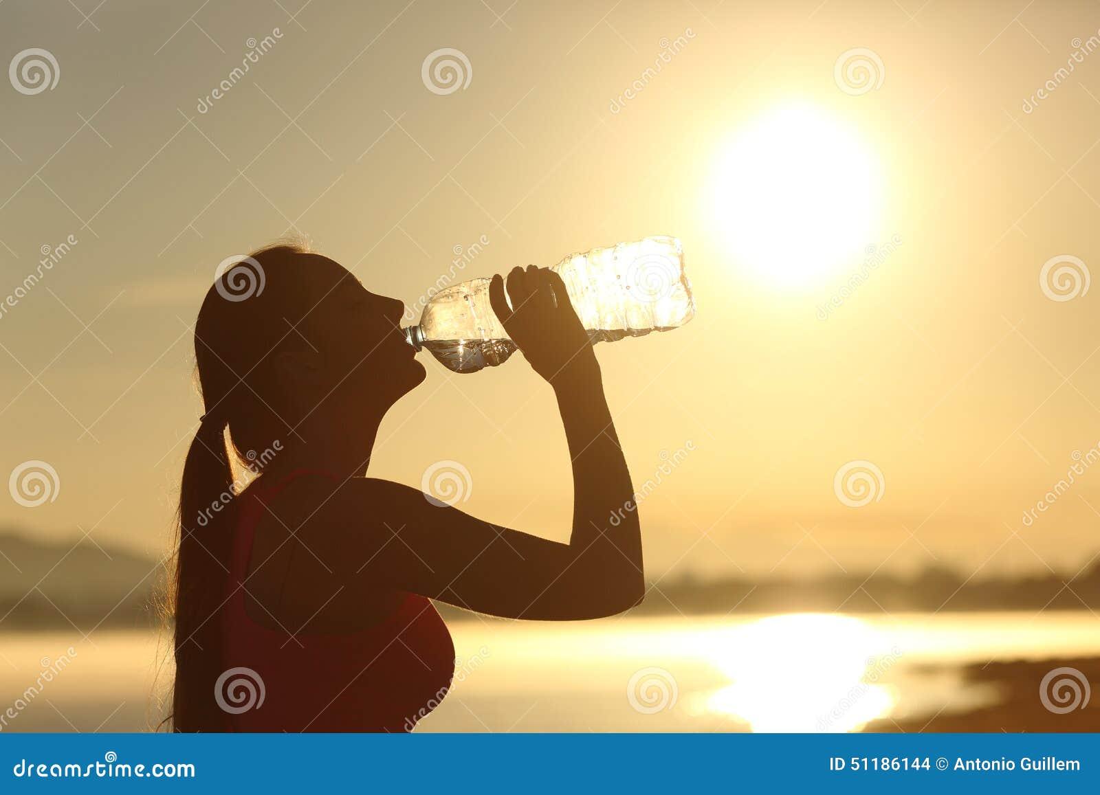 从瓶的健身妇女剪影饮用水