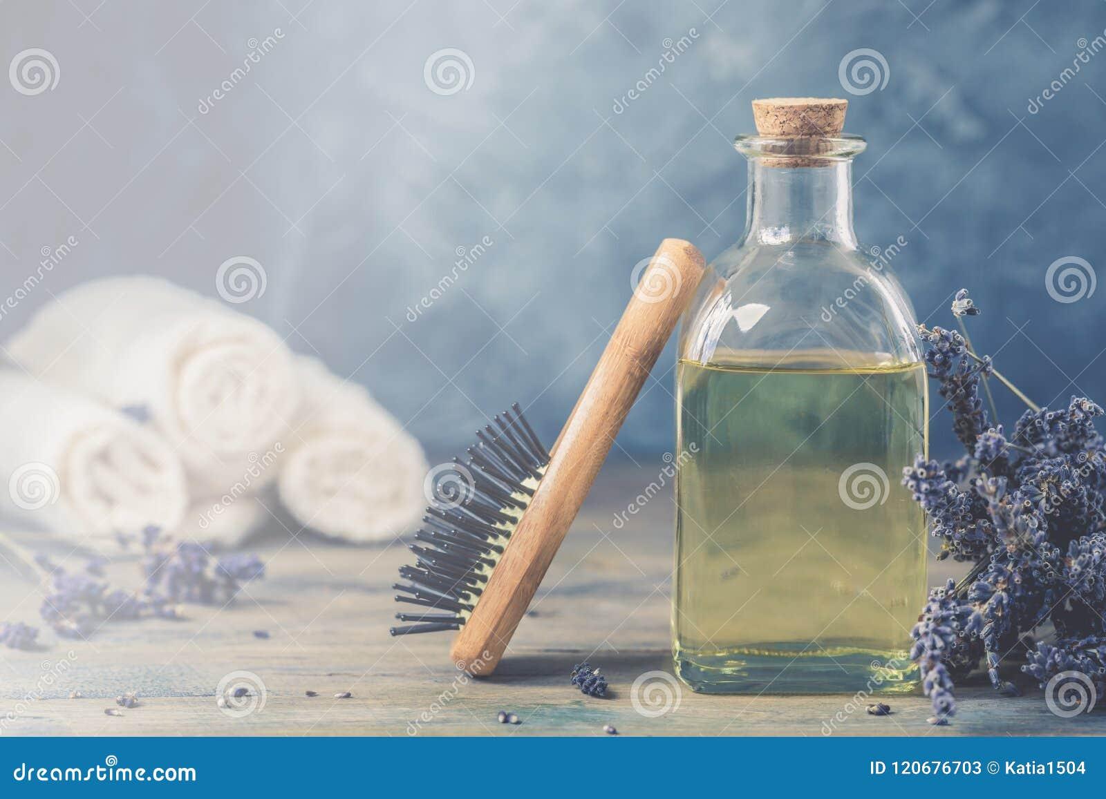 瓶自然化妆熏衣草油,头发和身体治疗,与一把木按摩梳子