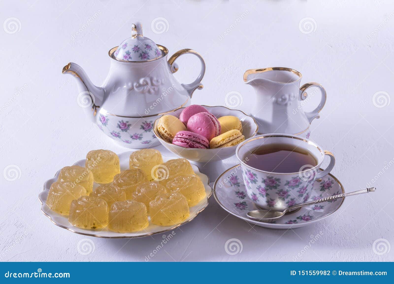 瓷茶具用牛奶、通心面和橘子果酱、牛奶罐、茶杯、茶杯,胶粘的糖果
