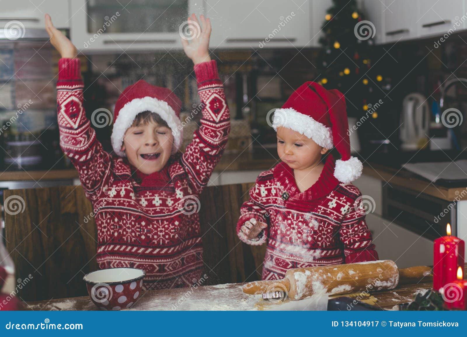 甜小孩孩子和他的哥哥,男孩,在家准备圣诞节曲奇饼的帮助的妈妈