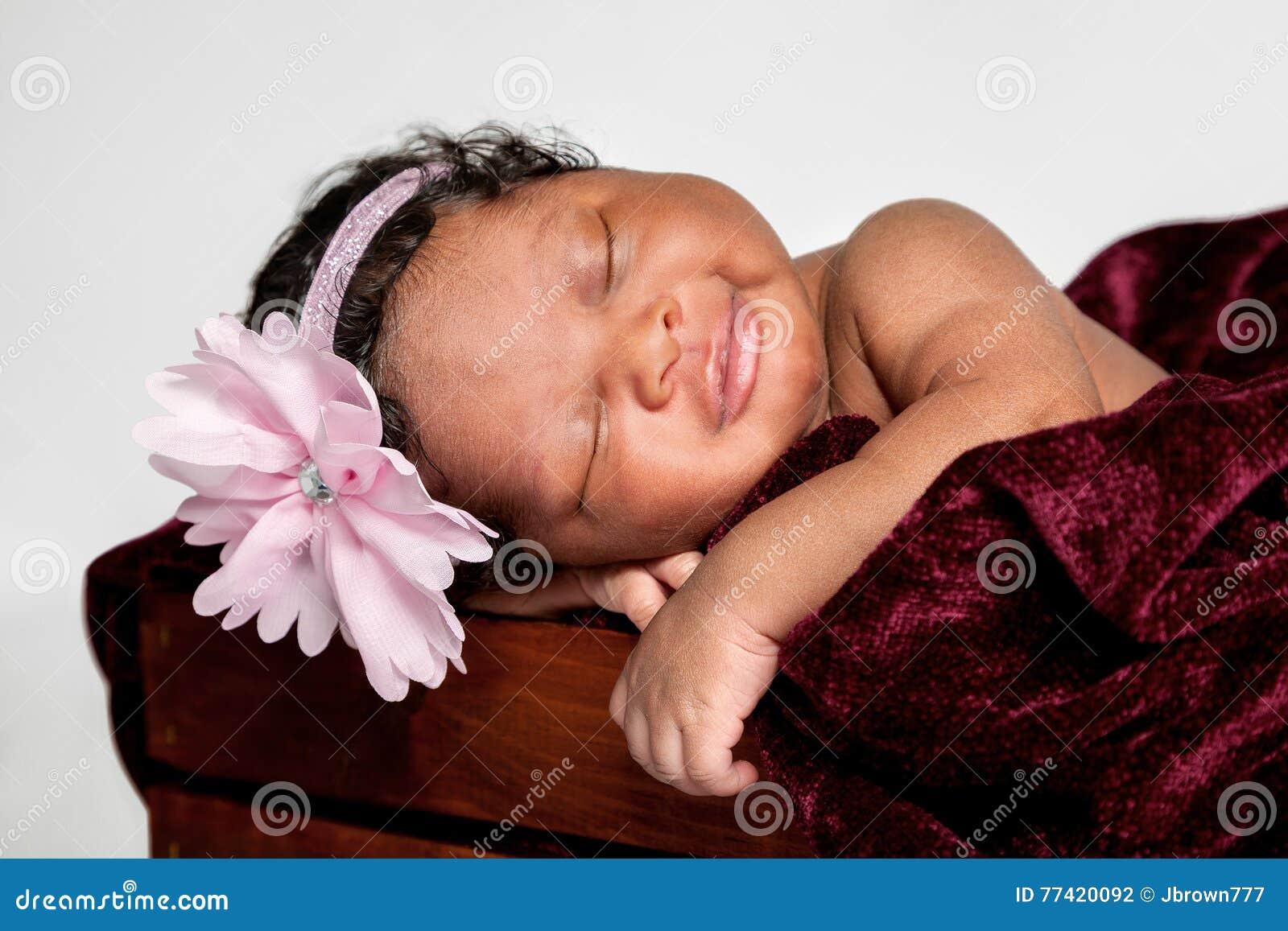 甜非裔美国人的婴孩睡着在一个木板箱
