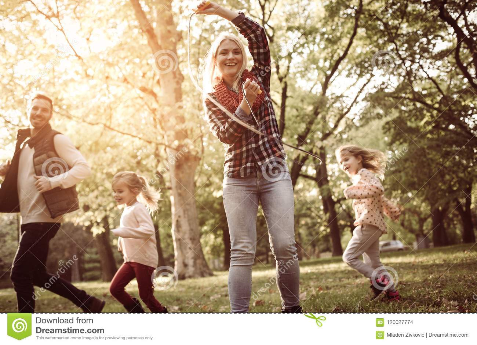 生与女儿低谷举行jum的公园母亲的赛跑