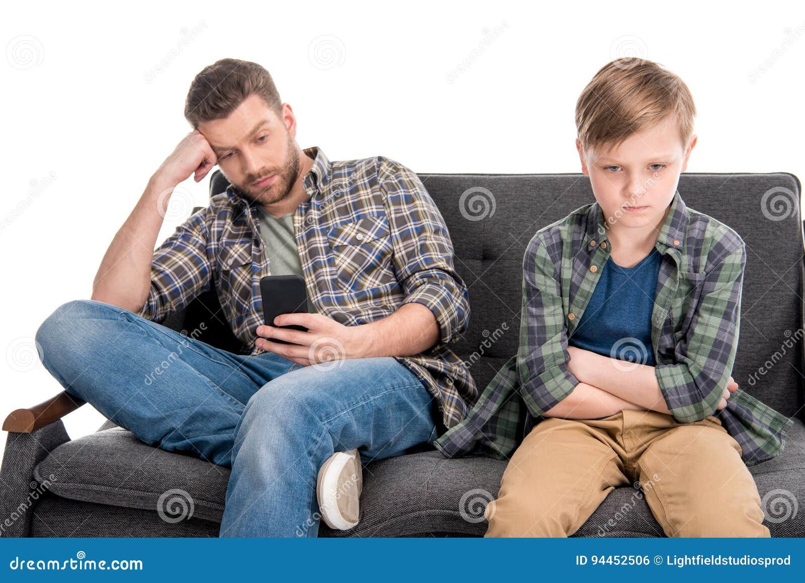 生使用智能手机并且让小儿子烦恼坐有横渡的胳膊的沙发