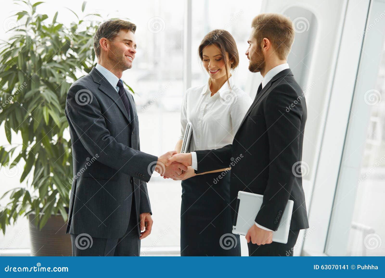生意人现有量震动 握手沟通与的人们