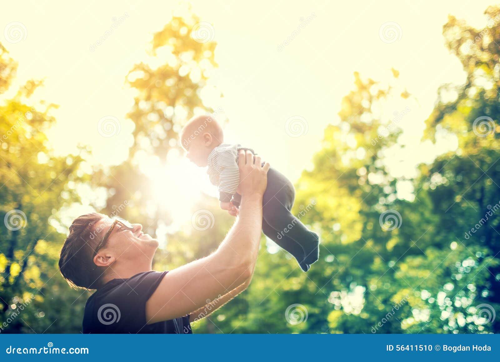 生拿着胳膊的小孩,投掷空气的婴孩 愉快的家庭的概念,反对光的葡萄酒作用