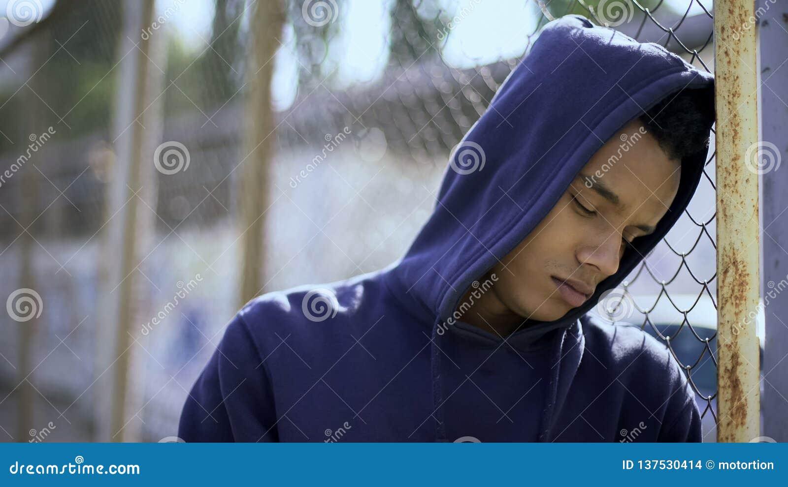 生气男孩倾斜在篱芭的,流浪儿分离从家庭和被扣留