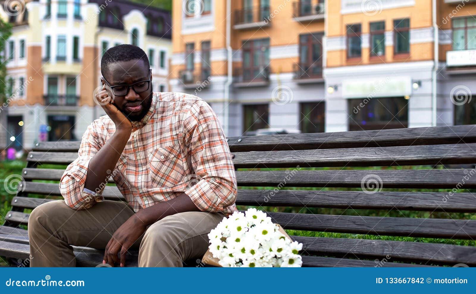 生气美国黑人人偏僻坐与花束,不合格的日期的城市长凳