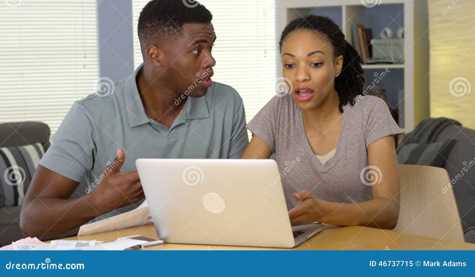 生气年轻黑夫妇争论关于票据和财务与膝上型计算机