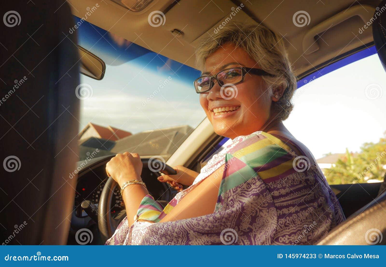 生活方式中部夏天画象变老了驾驶左手汽车微笑的愉快和可爱的优等的亚裔印度尼西亚妇女快乐
