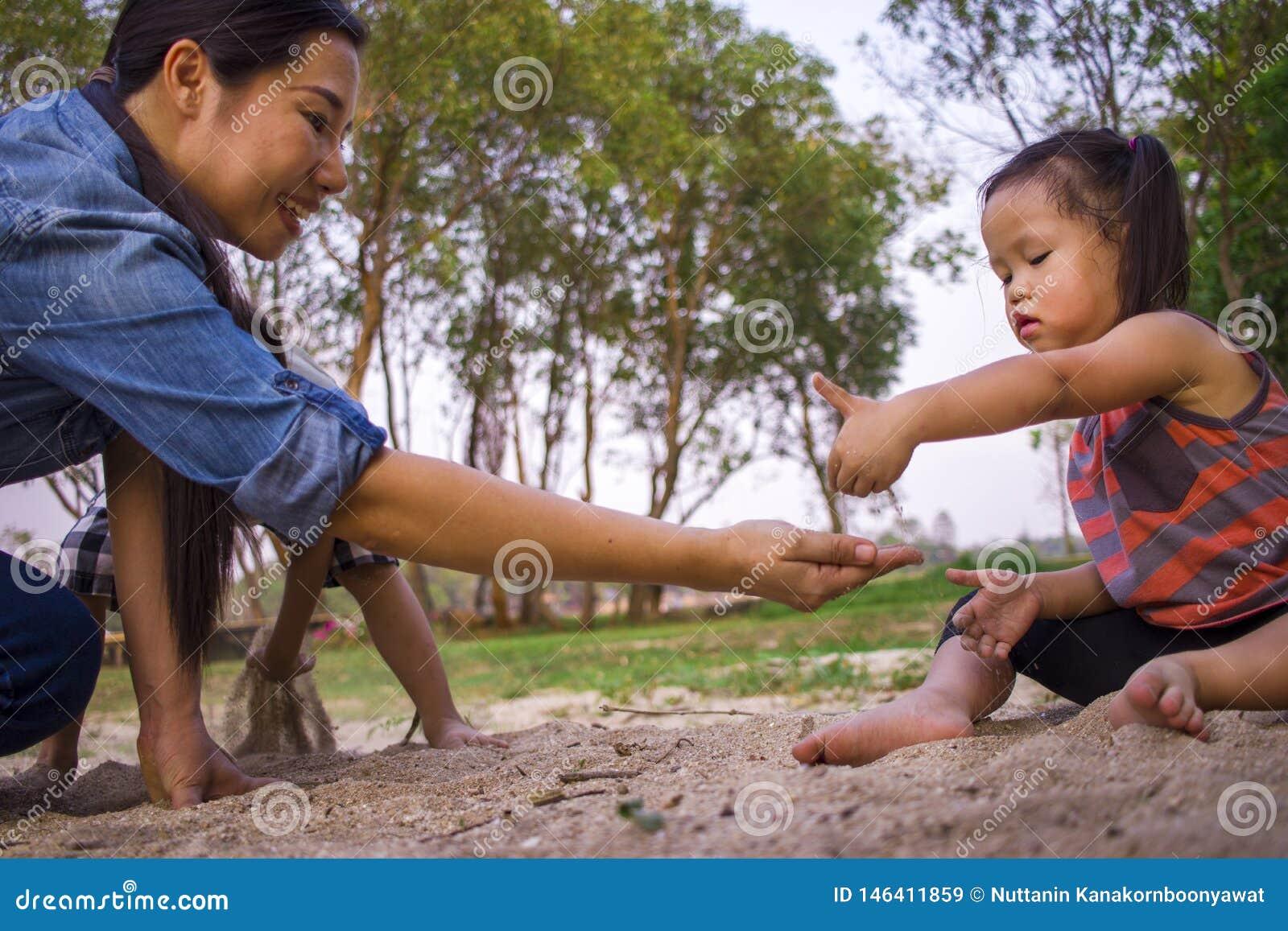 生活方式画象使用与沙子的妈妈儿子和女儿,滑稽的亚洲家庭在公园