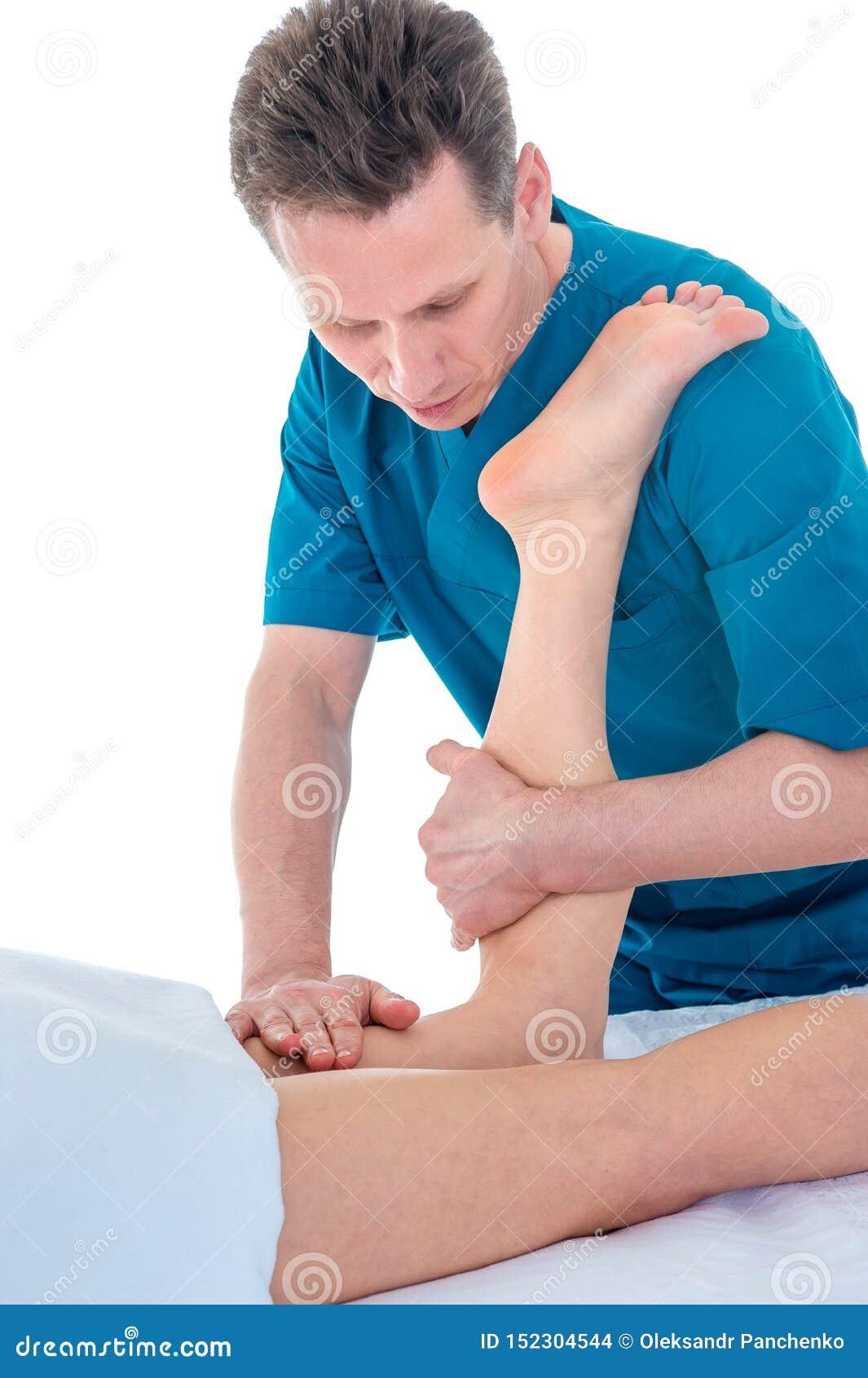 生理治疗师,按摩患者的腿在物理疗法屋子,物理疗法修复的概念