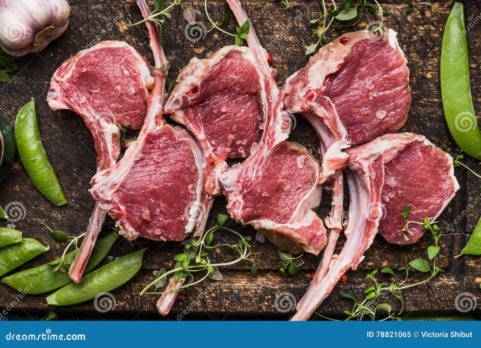 生肉放在架子上的羊羔和绿豆在黑暗的木背景,顶视图