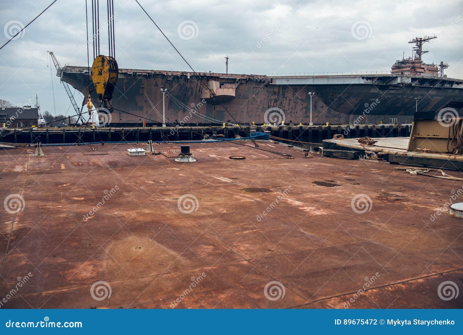 生锈的金属平台工业背景在船坞口岸的与战舰