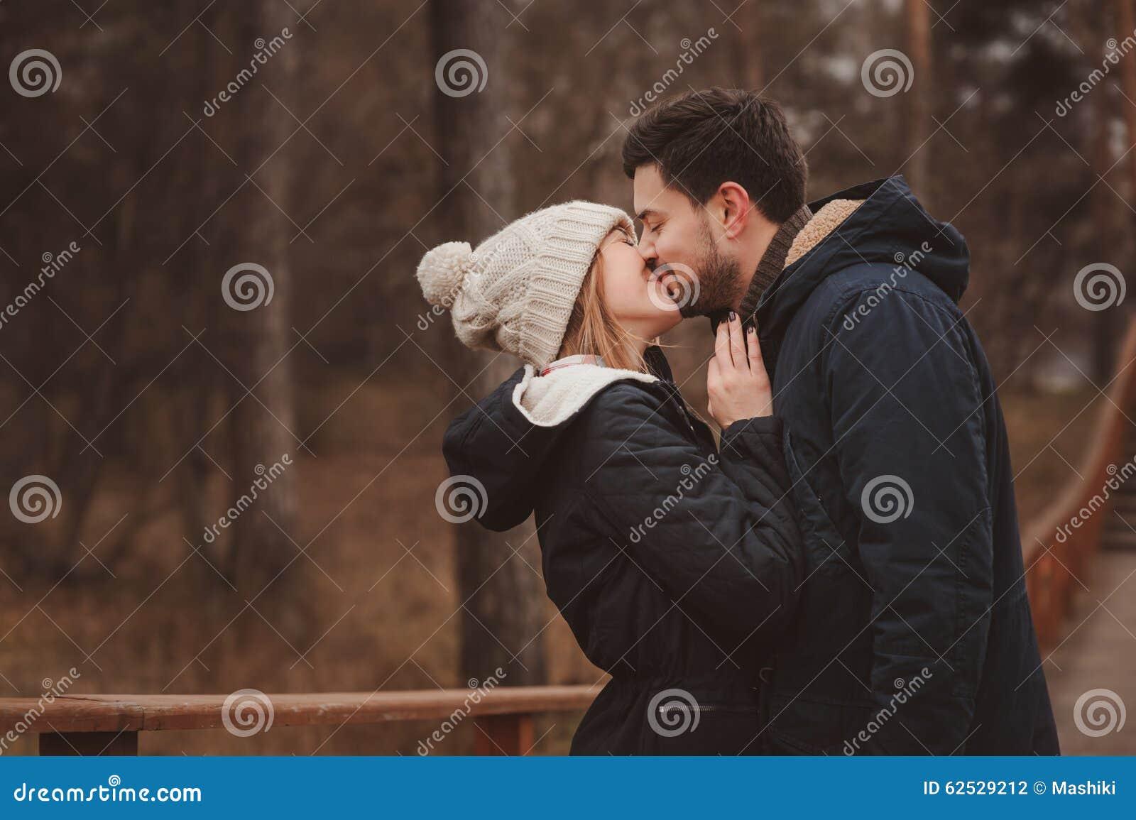 生活方式捕获愉快夫妇亲吻室外在舒适在森林里温暖步行