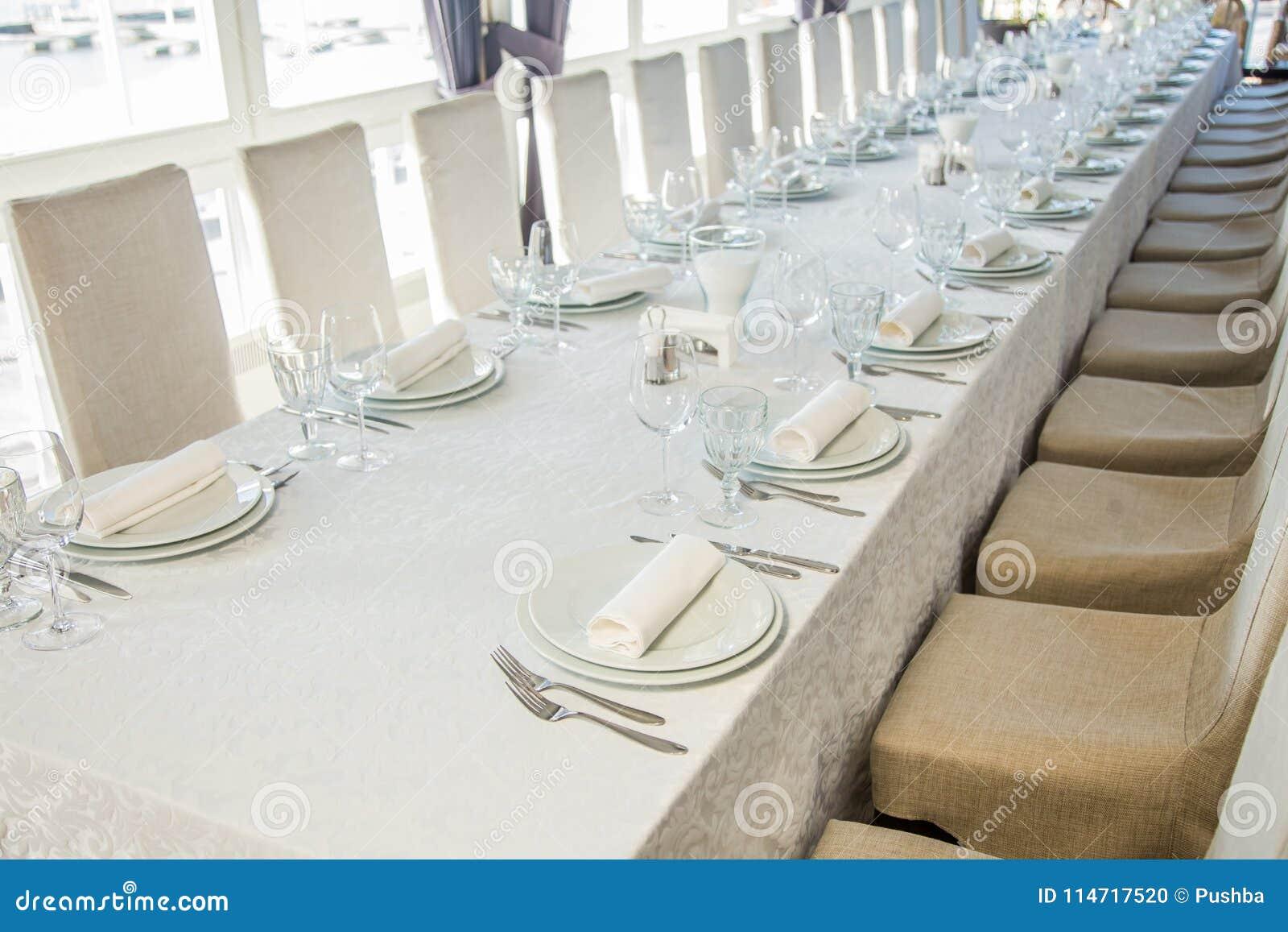 用与利器和玻璃的一张白色桌布盖的一张长的桌