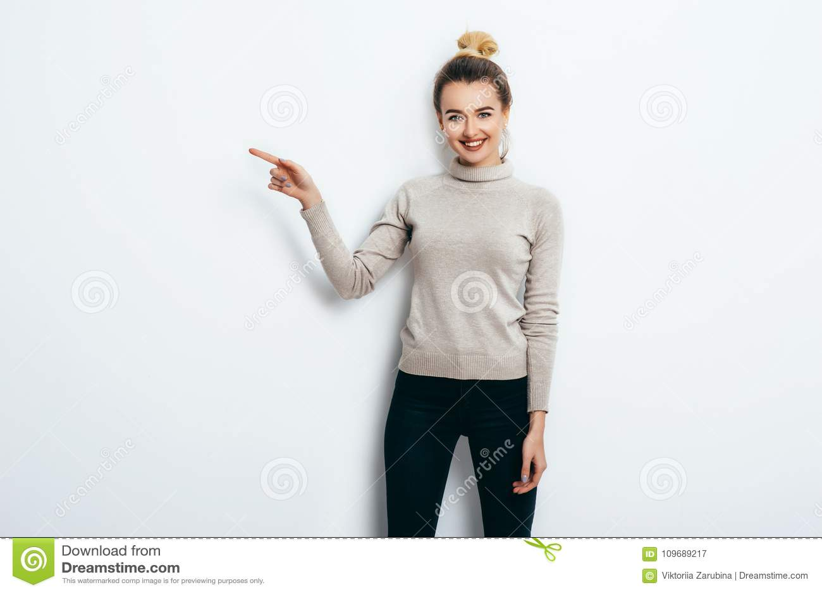用头发小圆面包佩带在牛仔裤和毛线衣指向与在拷贝空间的食指的年轻美丽的快乐的妇女在白色墙壁