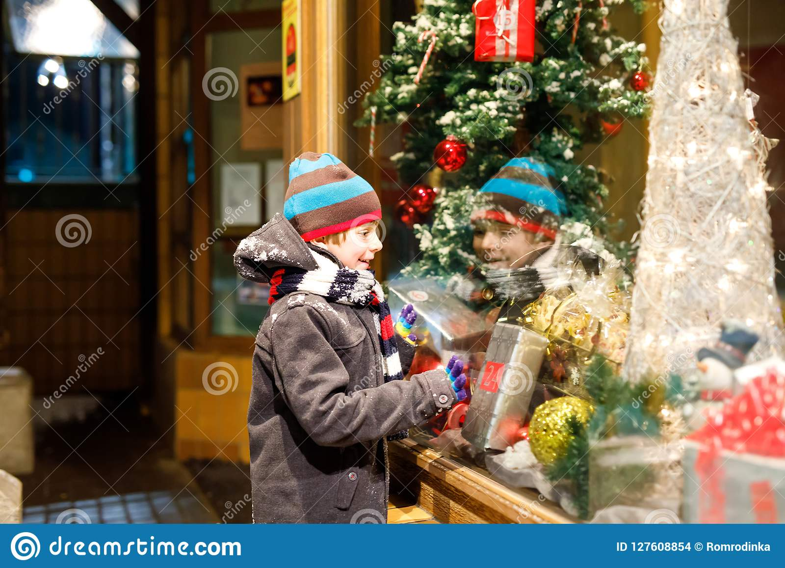 用礼物在时尚冬天给做窗口购物穿衣装饰的滑稽的愉快的孩子, xmas树