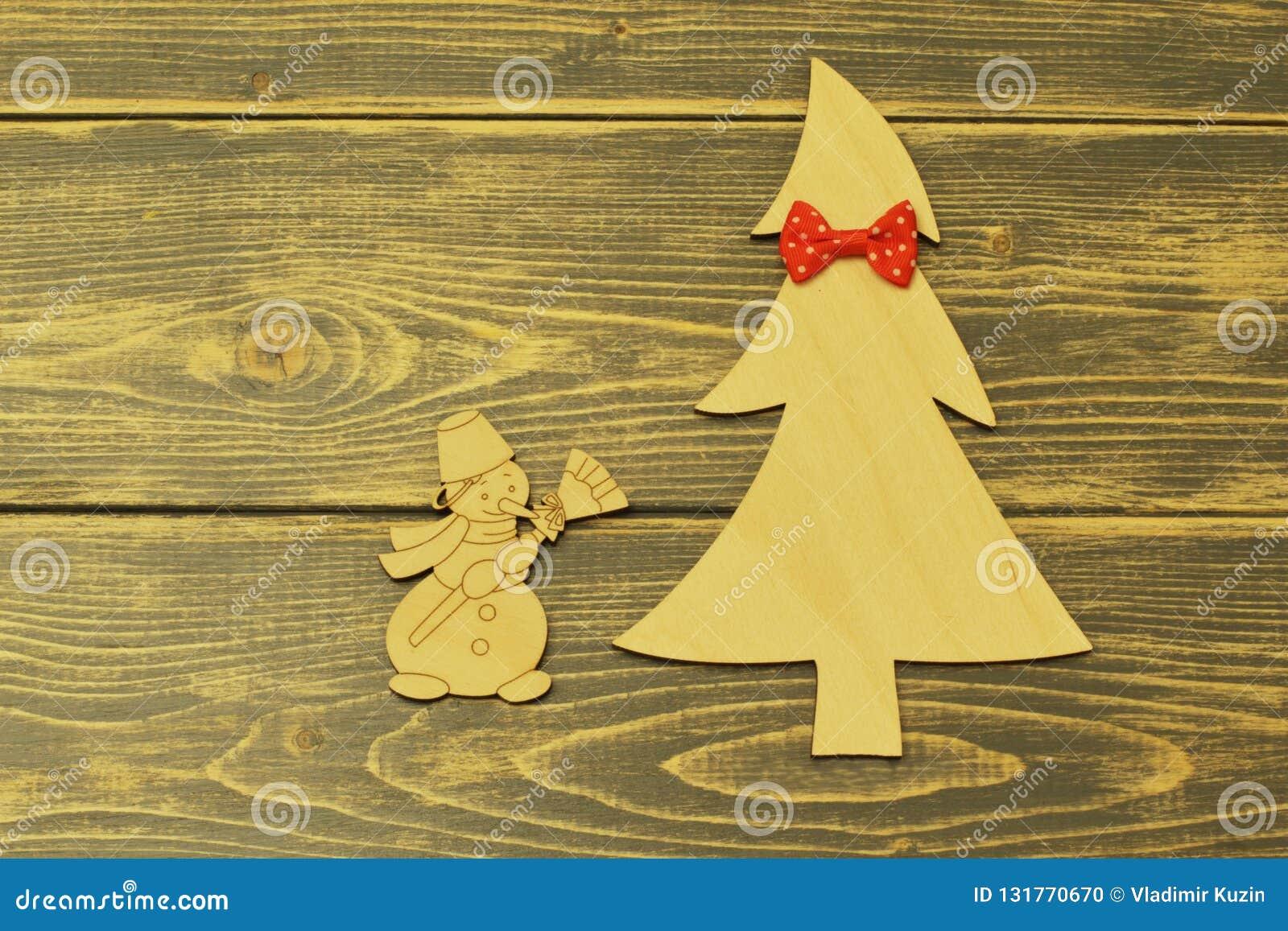用红色蝶形领结和快乐的葡萄酒雪人装饰的木圣诞树与笤帚在老木黑暗的背景
