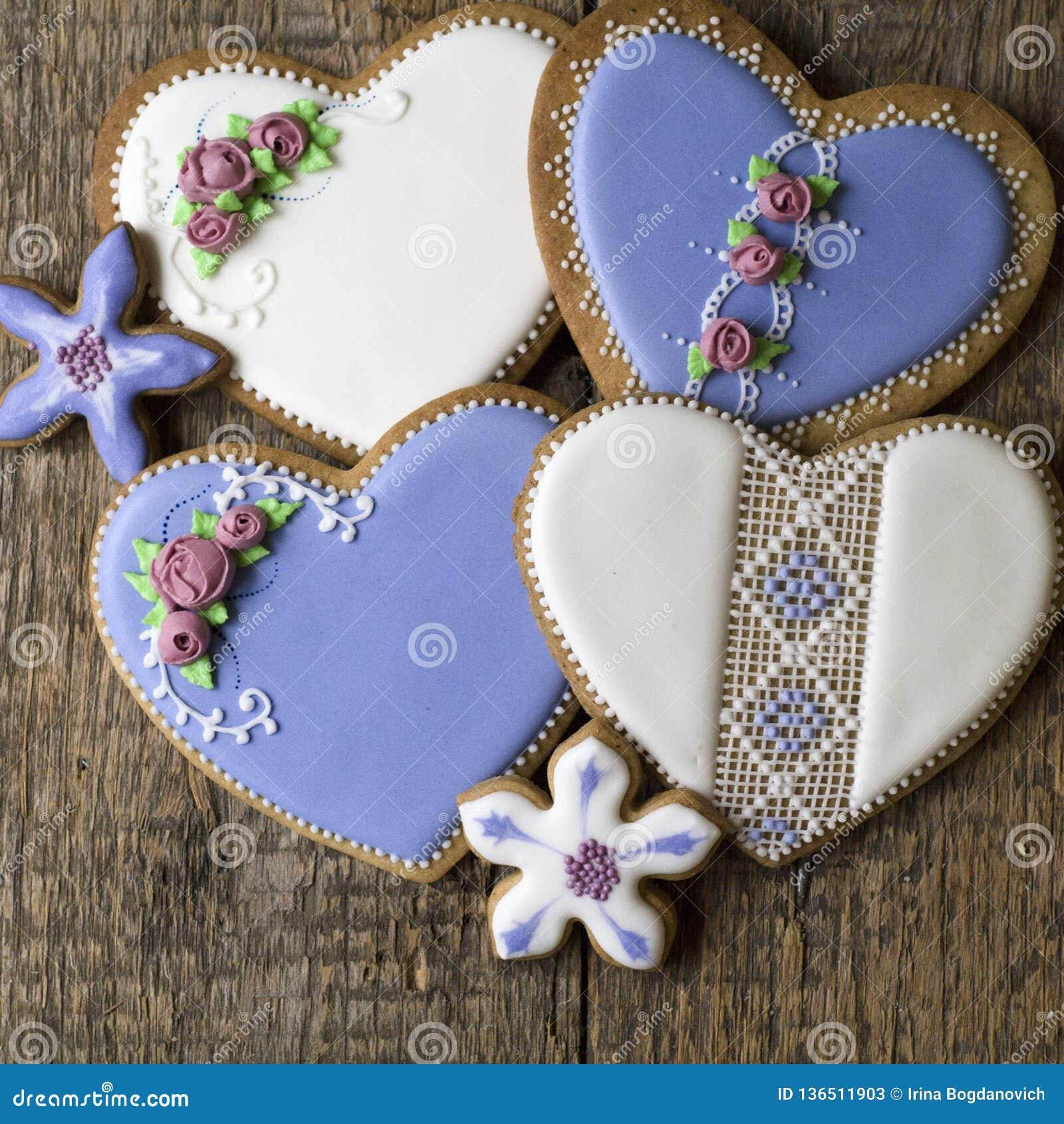用花和刺绣装饰的白色和淡紫色心形的曲奇饼在葡萄酒样式在木背景华伦泰的