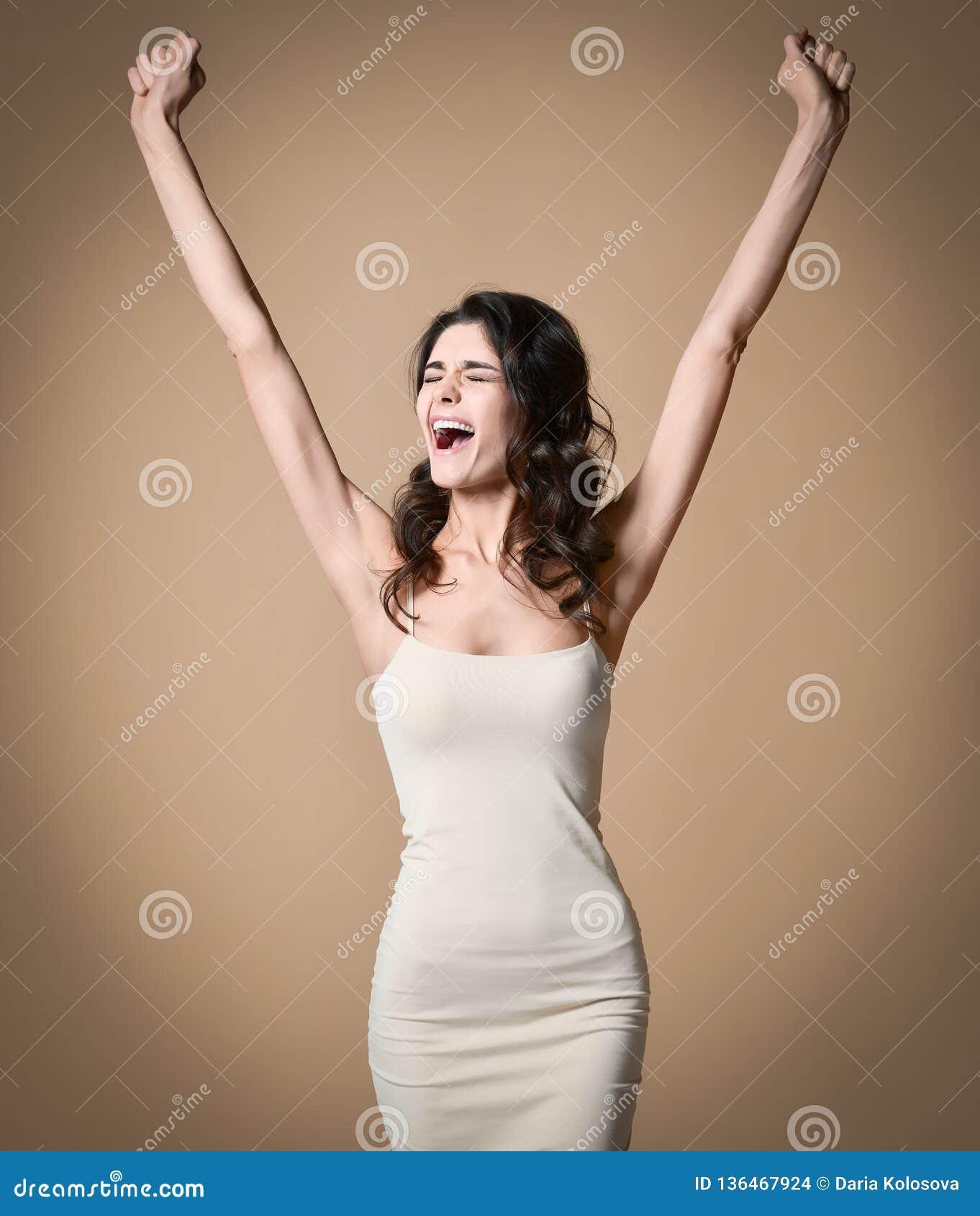用被举的手呼喊和庆祝成功的愉快的成功的年轻女人