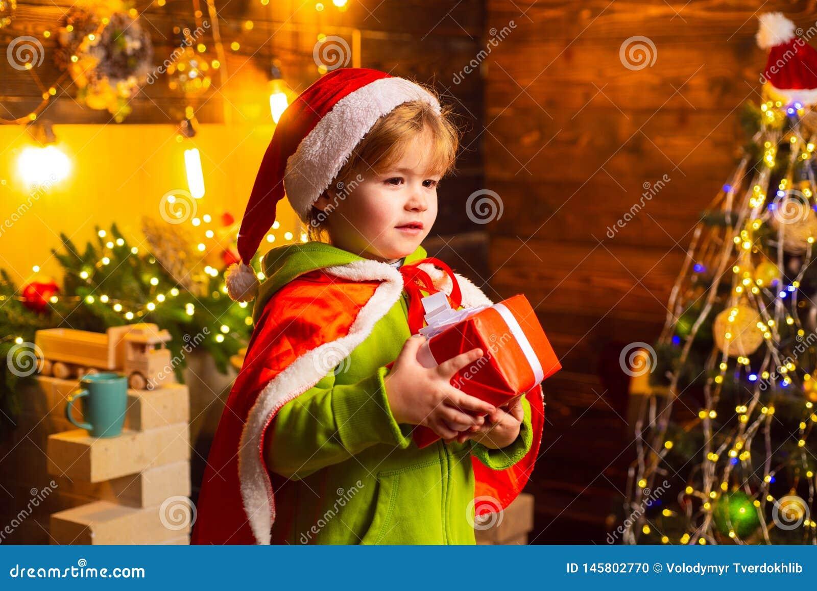 由圣诞树的愉快的小男孩与他的圣诞礼物 小孩穿圣诞老人衣裳 o