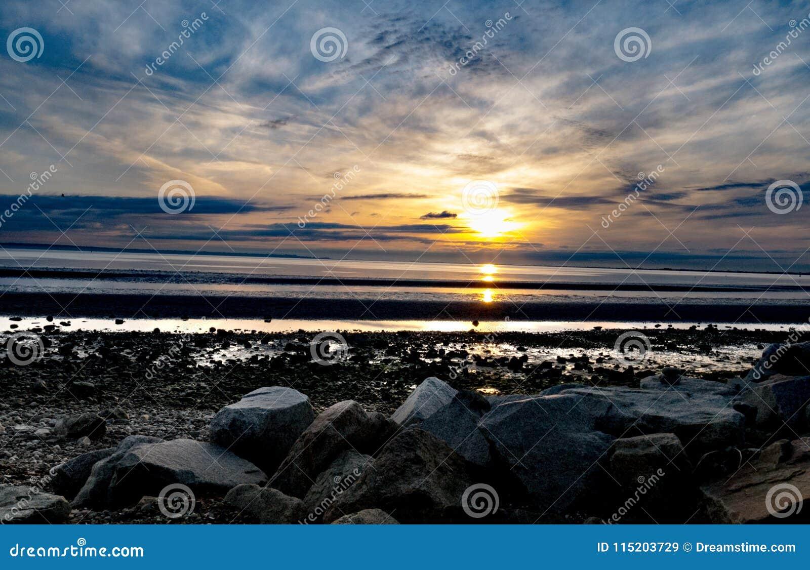 由日落的多岩石的海滩