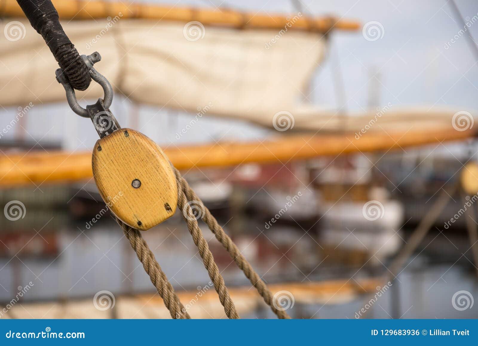 由木头和绳索的滑轮做的风帆在一艘老帆船,有风帆和其他小船的从焦点在背景中