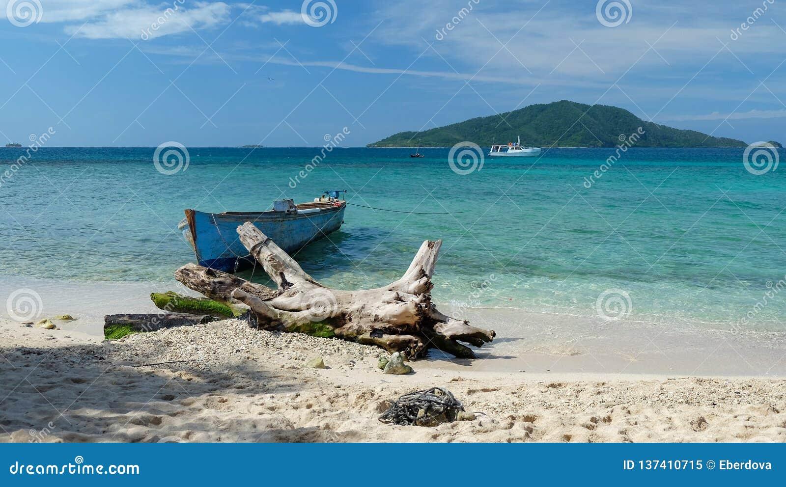 由海滩的一老渔船在一块清楚的蓝色绿松石
