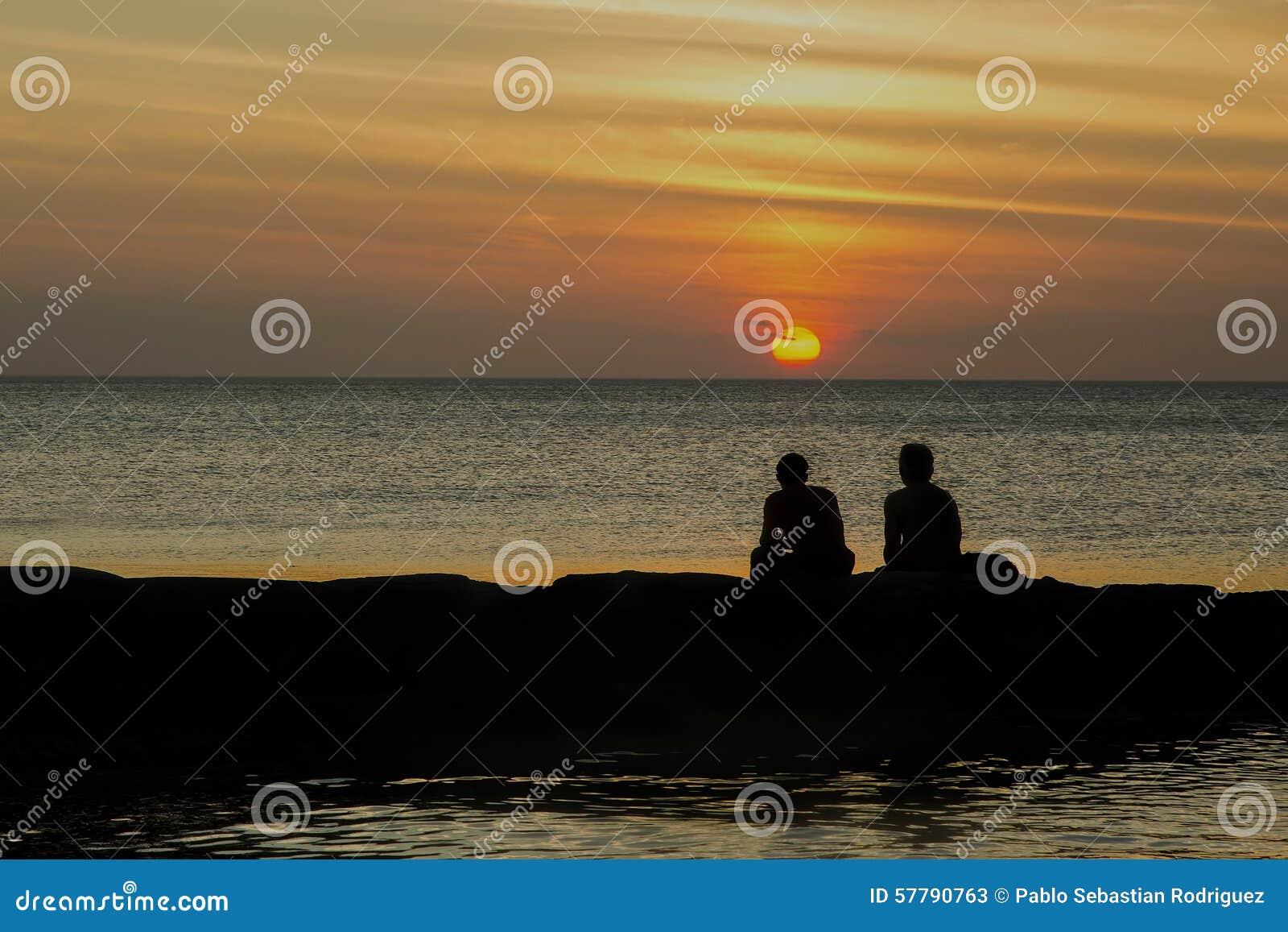 由海的两个朋友享受日落的