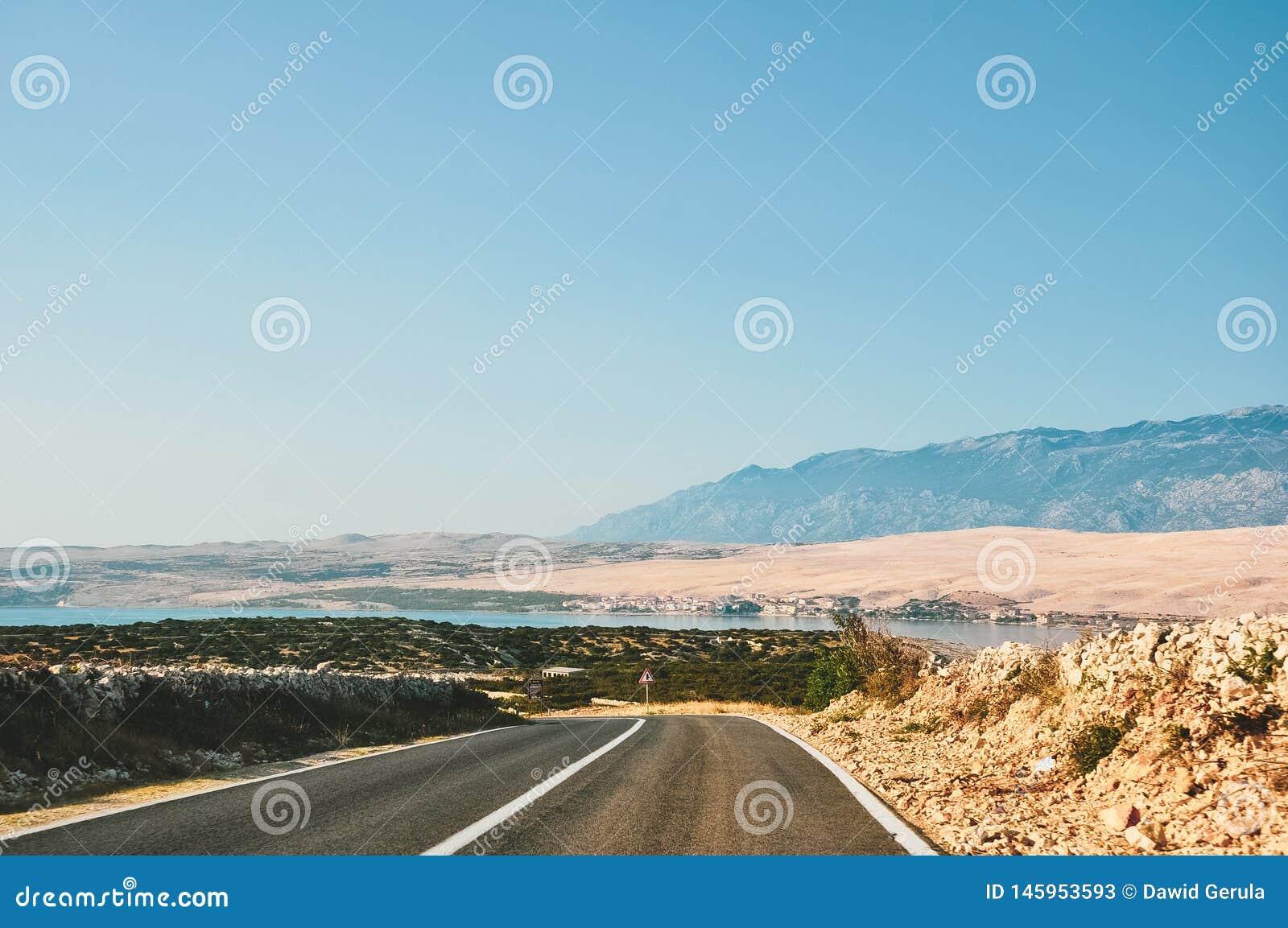 由海的风景路在导致Pag的克罗地亚,在海岛上,有山的在背景中