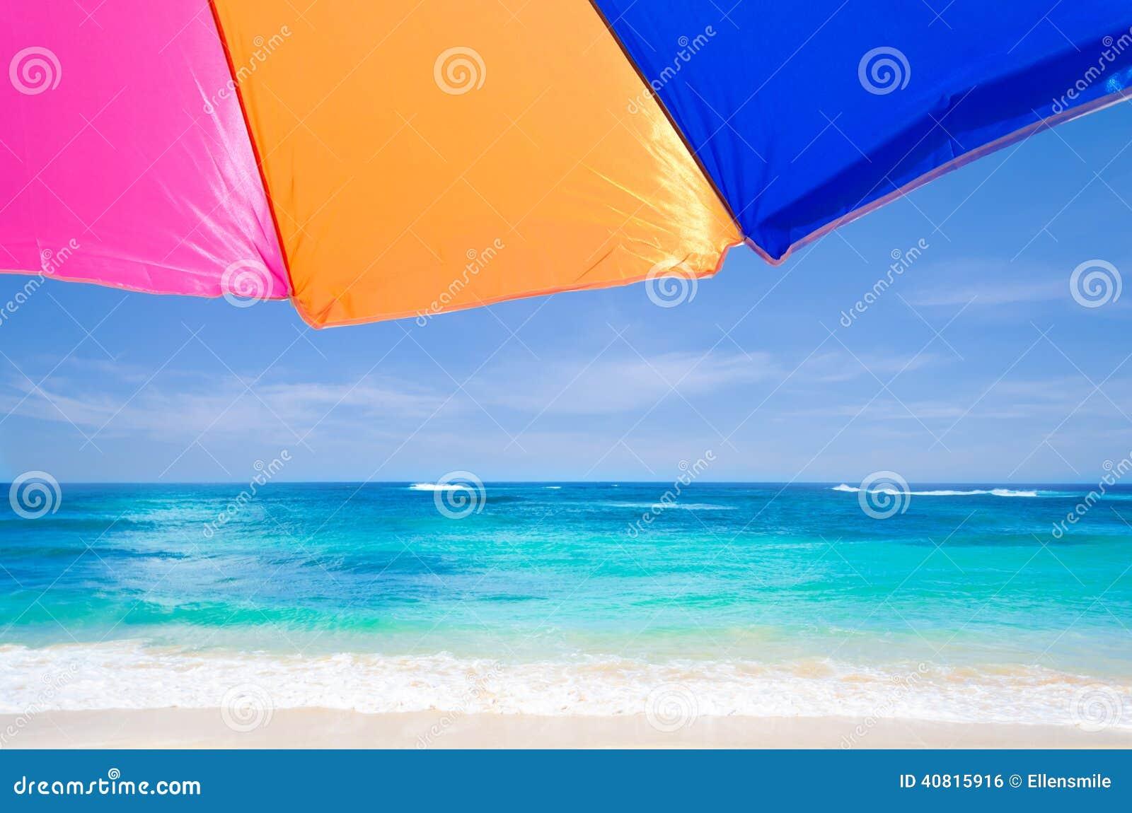 反对蓝天和海洋的沙滩伞的背景.图片