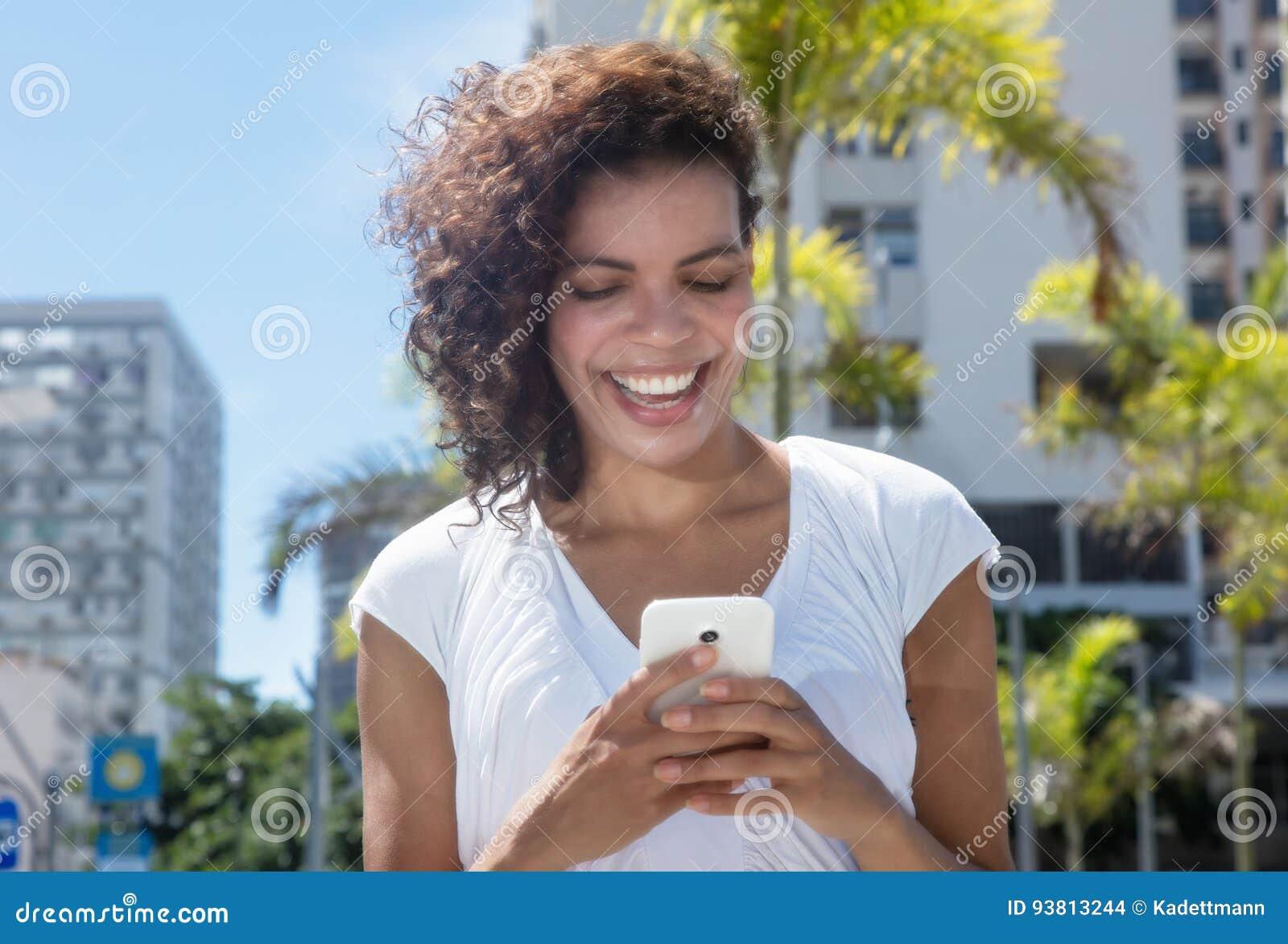 由电话的美好的年轻西班牙妇女传讯