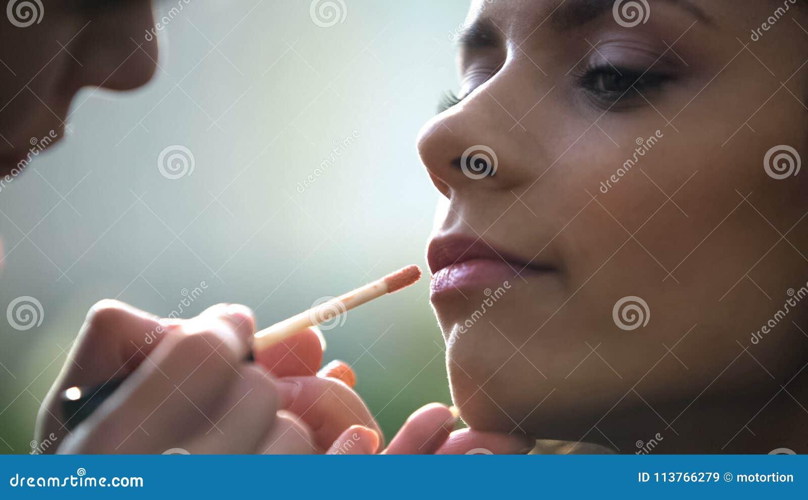 申请嘴唇光泽的化妆师的手,美丽的新娘为婚姻做准备