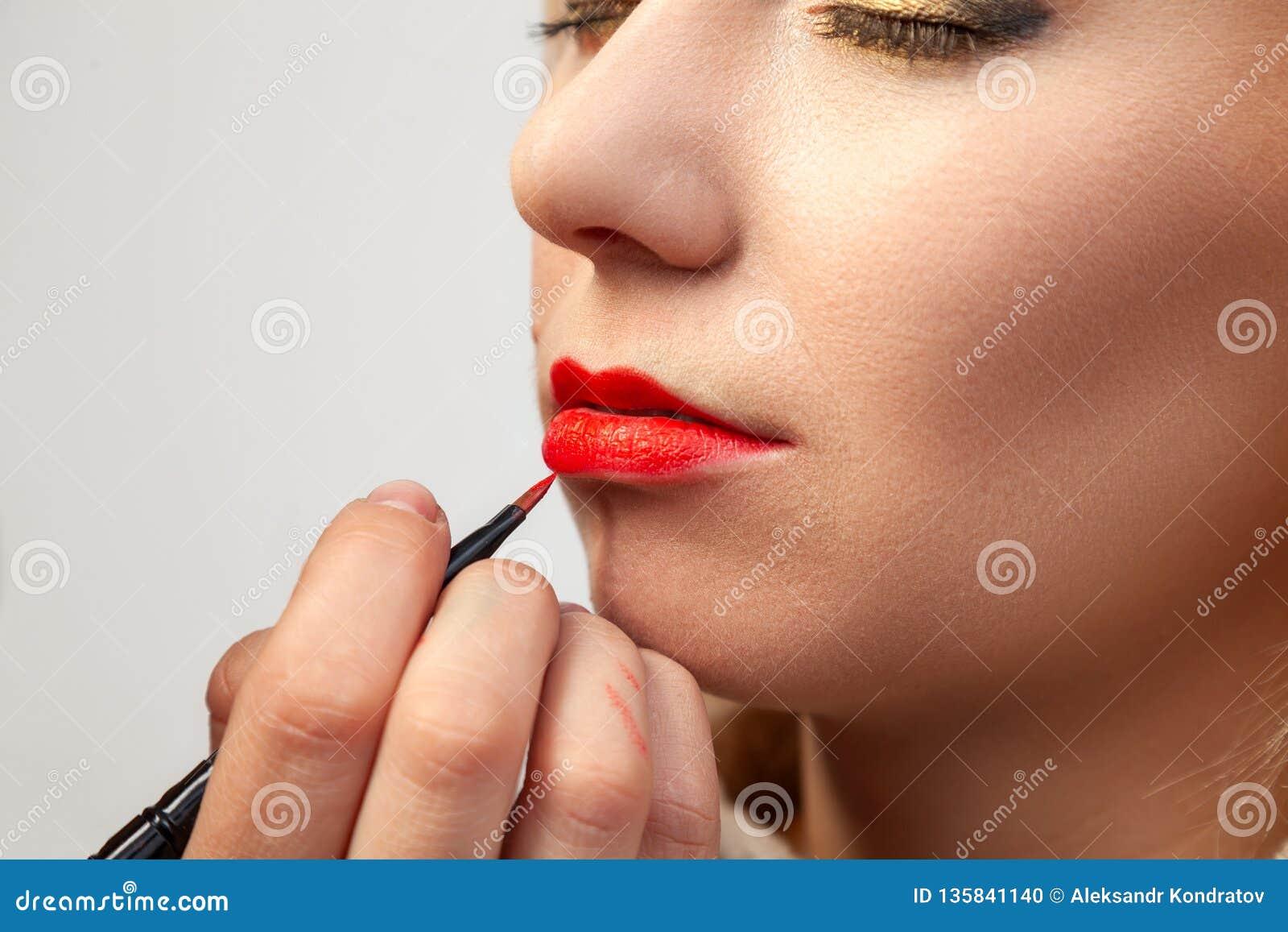 申请在模型的嘴唇的构成特写镜头,化妆师在她的手上拿着一把刷子并且应用红色口红,