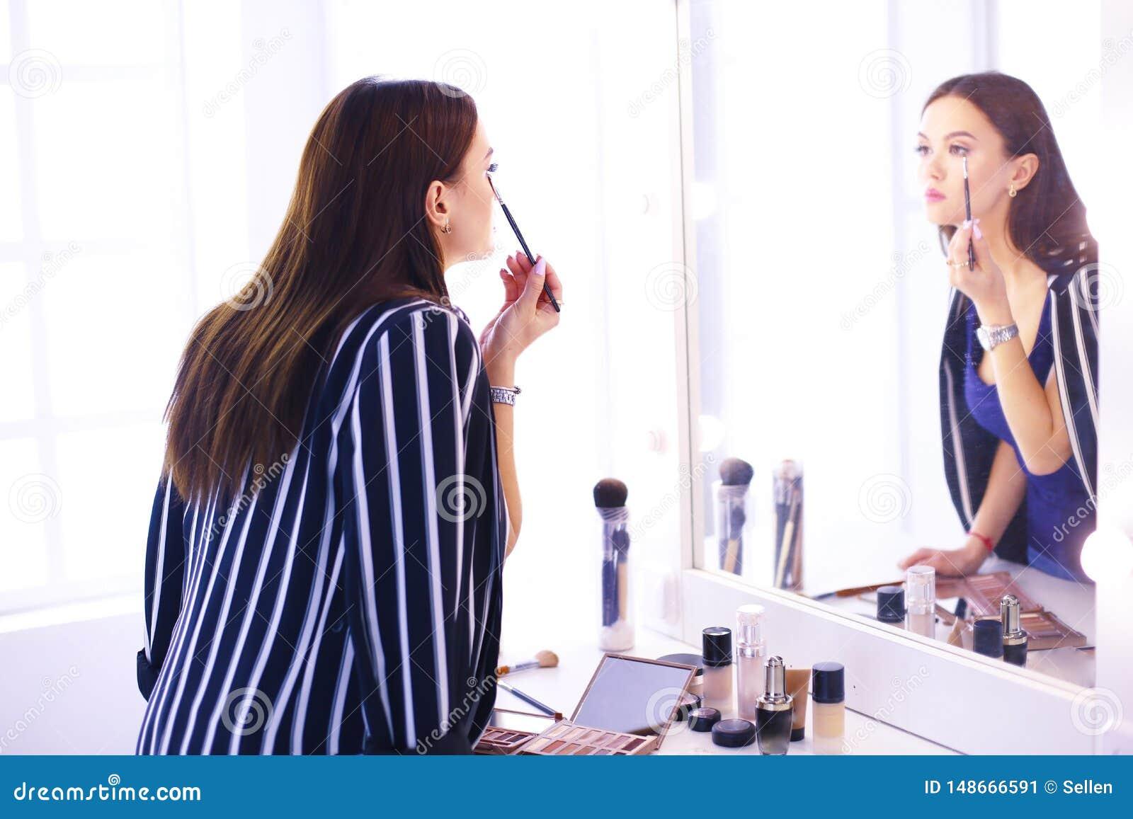申请她的构成的年轻美女的反射,看在镜子