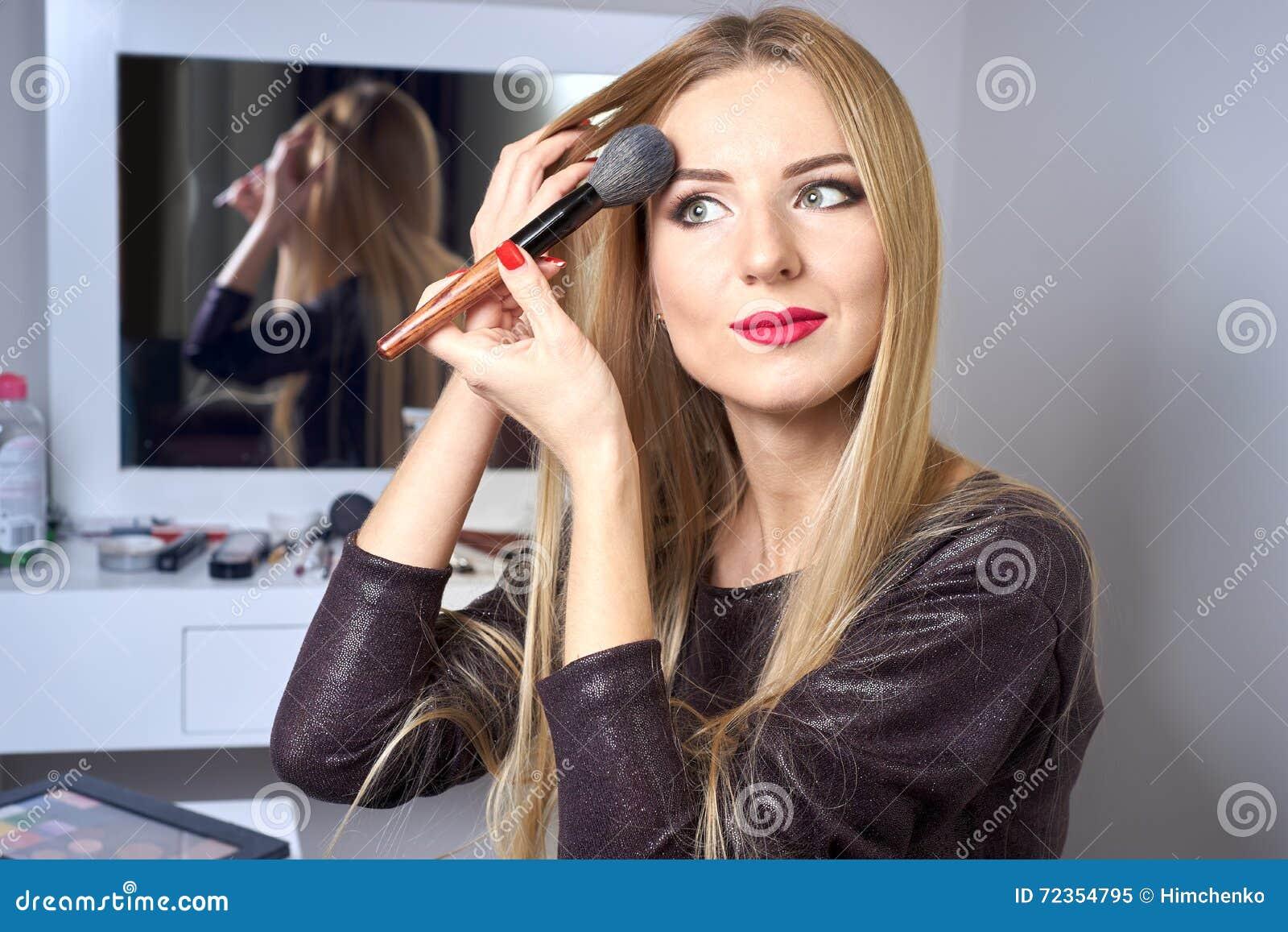 申请她的构成的年轻美丽的妇女的反射