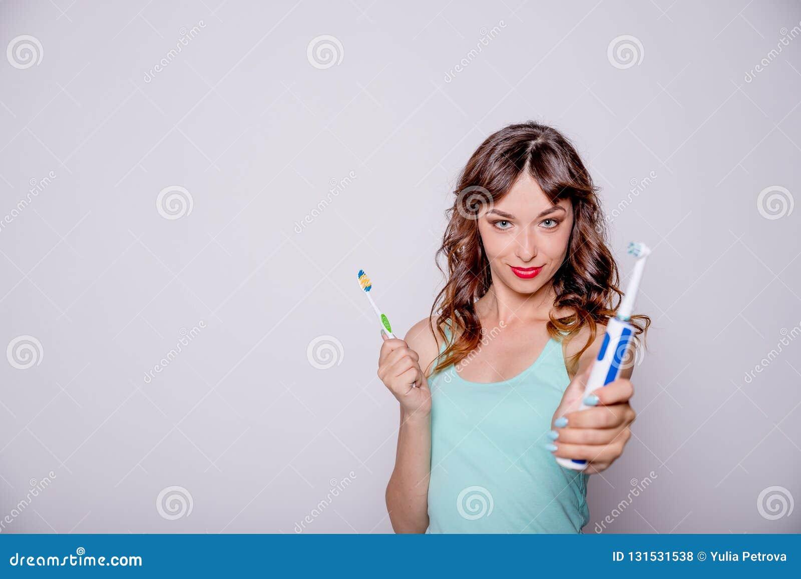 电和传统牙刷 口腔的卫生学 一年轻美女选择在电之间和