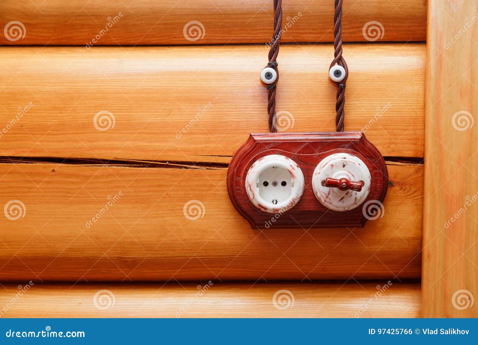 电子插口和开关在减速火箭的样式在木墙壁上 电工设计在房子里