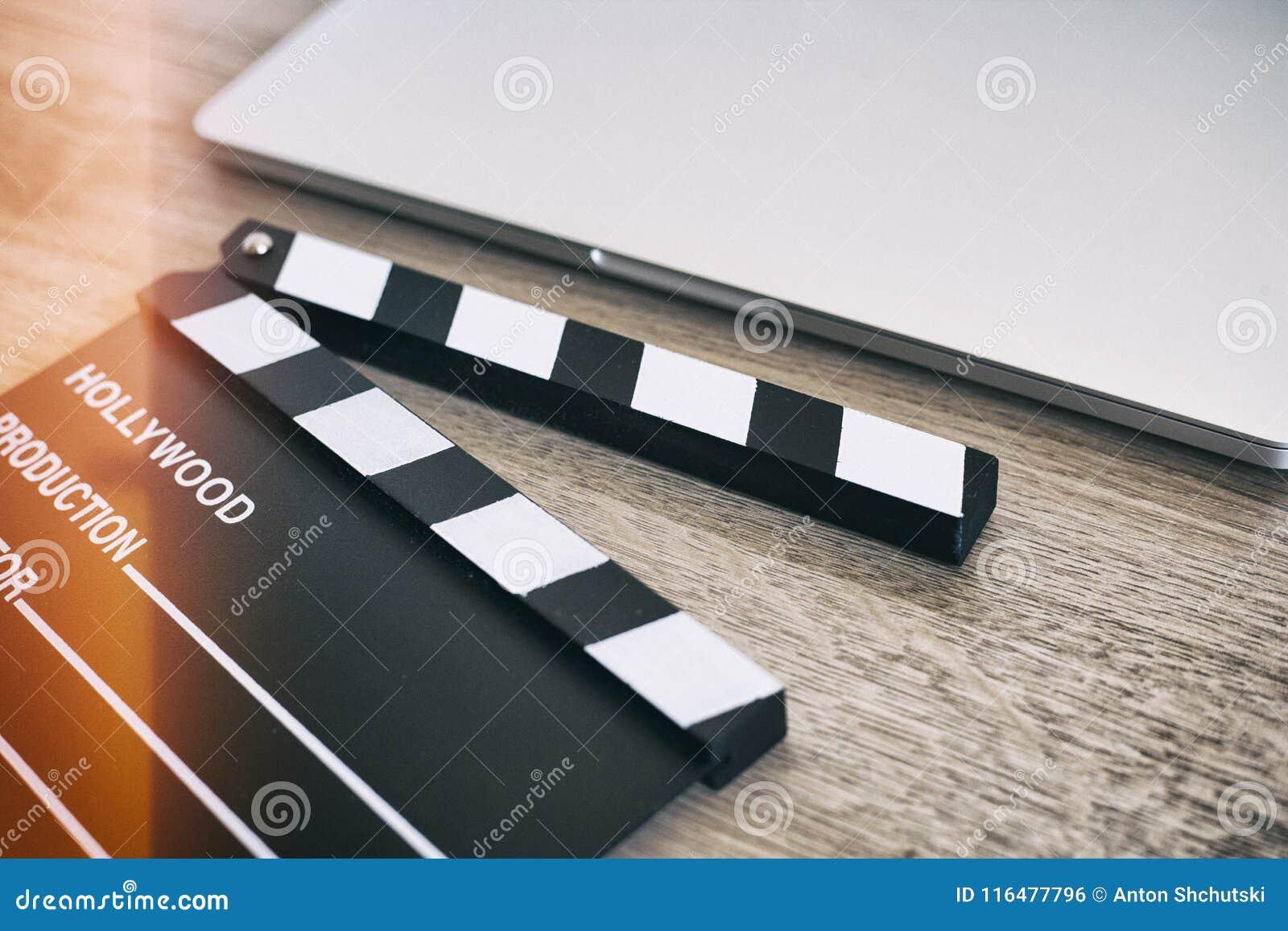 电影拍板和膝上型计算机在木头