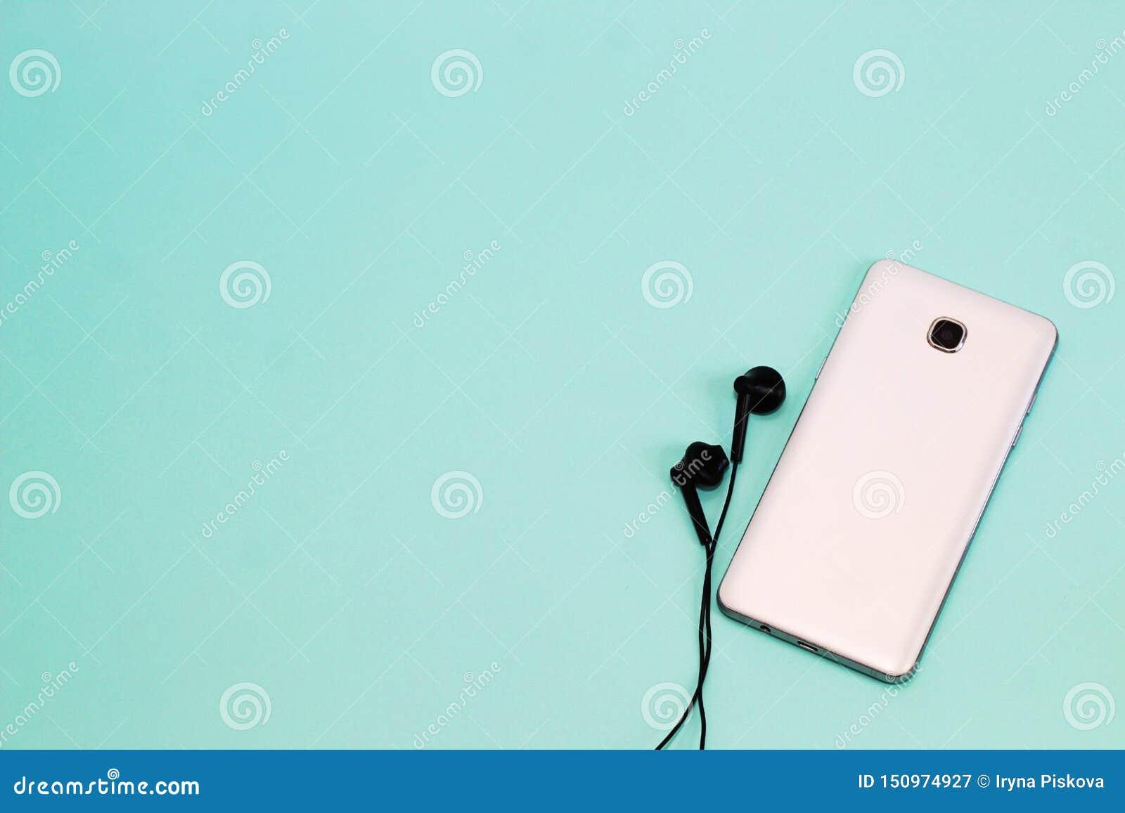 电话和耳机在轻的背景 与空间的背景文本的