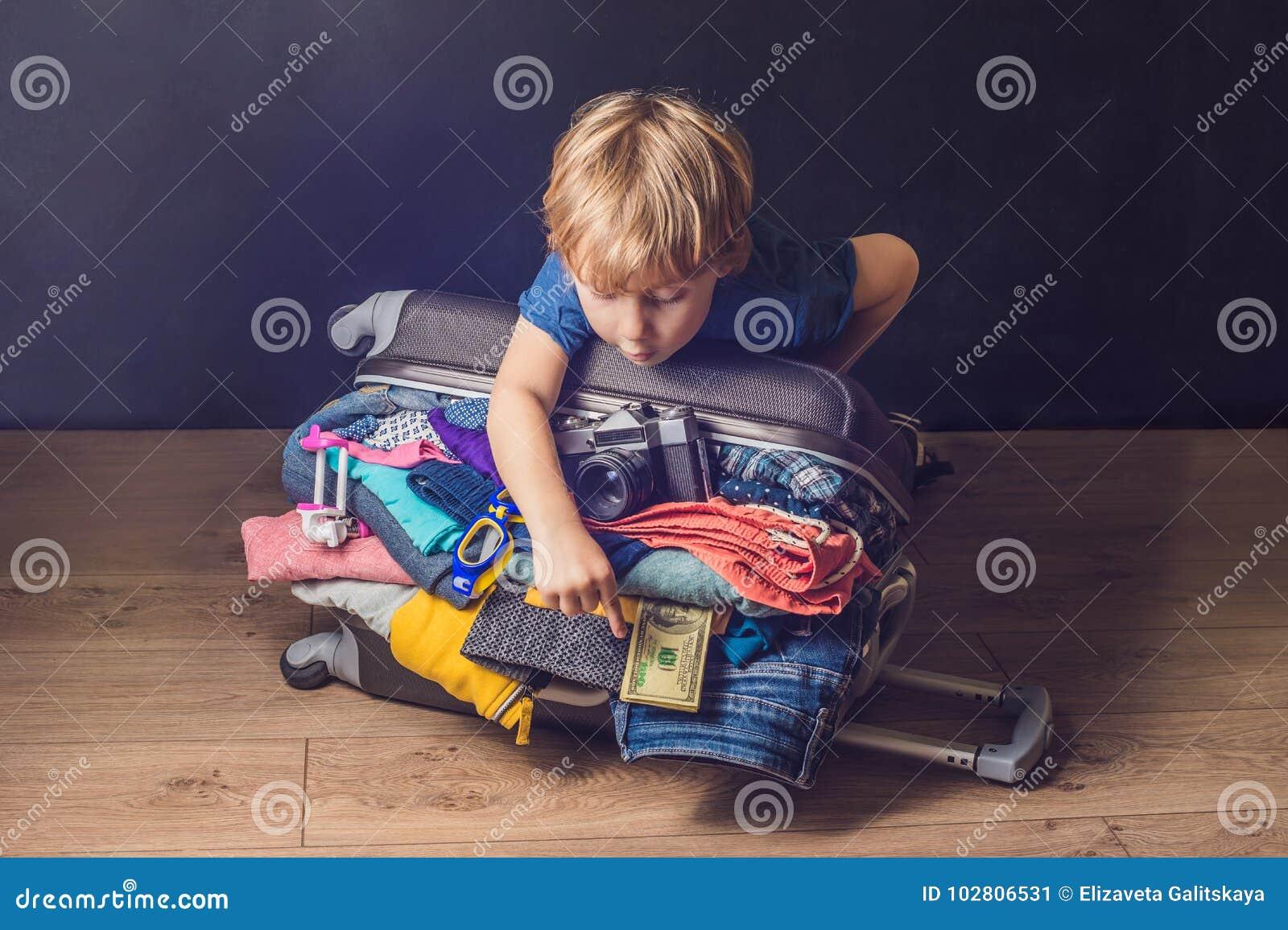 男婴和旅行手提箱 为Vacatio和行李包装的孩子