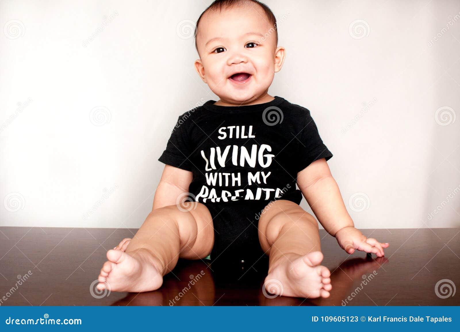 男婴穿有消息的一件衬衣说他与我的父母仍然居住