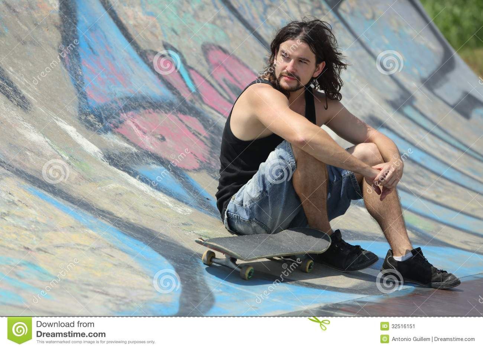男孩与滑板坐一个半管子