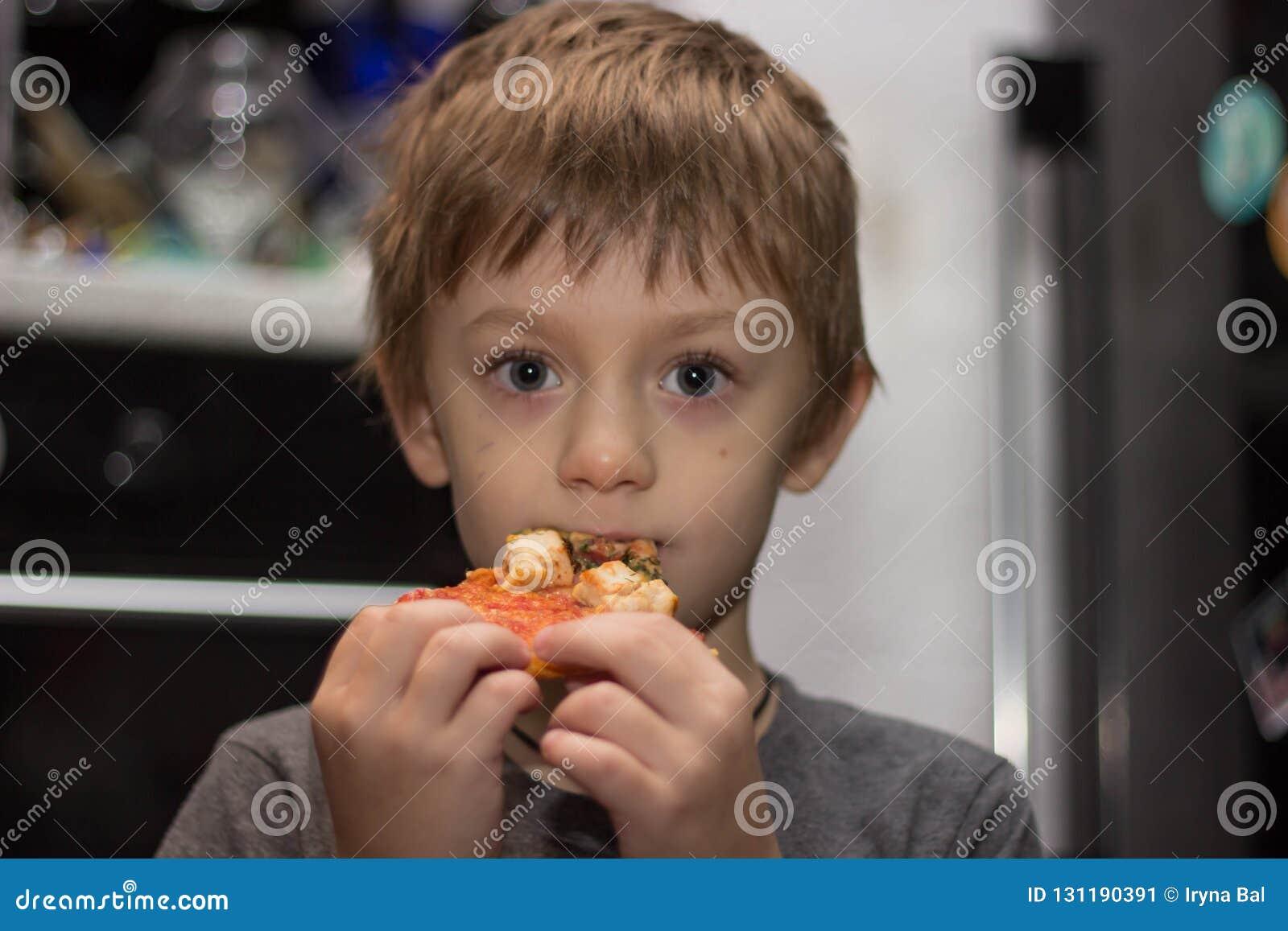 男孩吃一非常鲜美比萨高兴地巨大