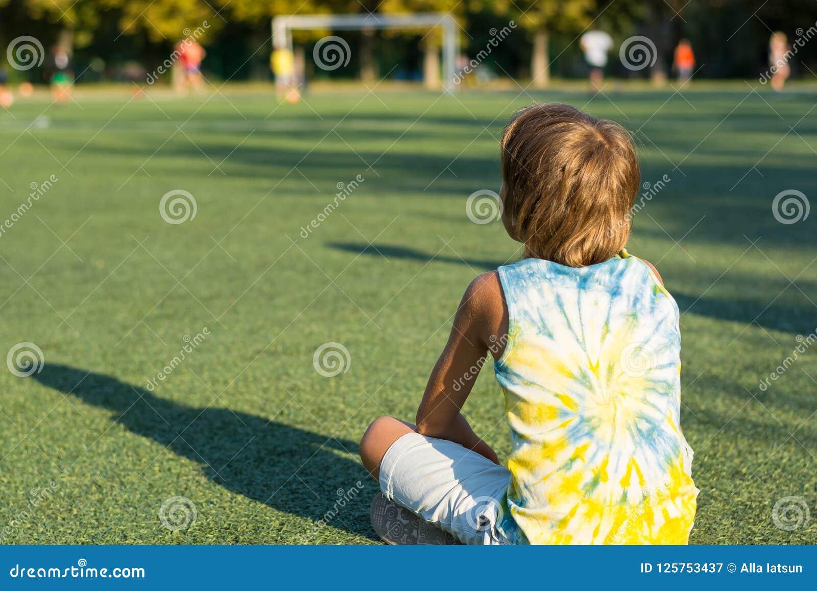 男孩后面坐草在的体育场的边缘