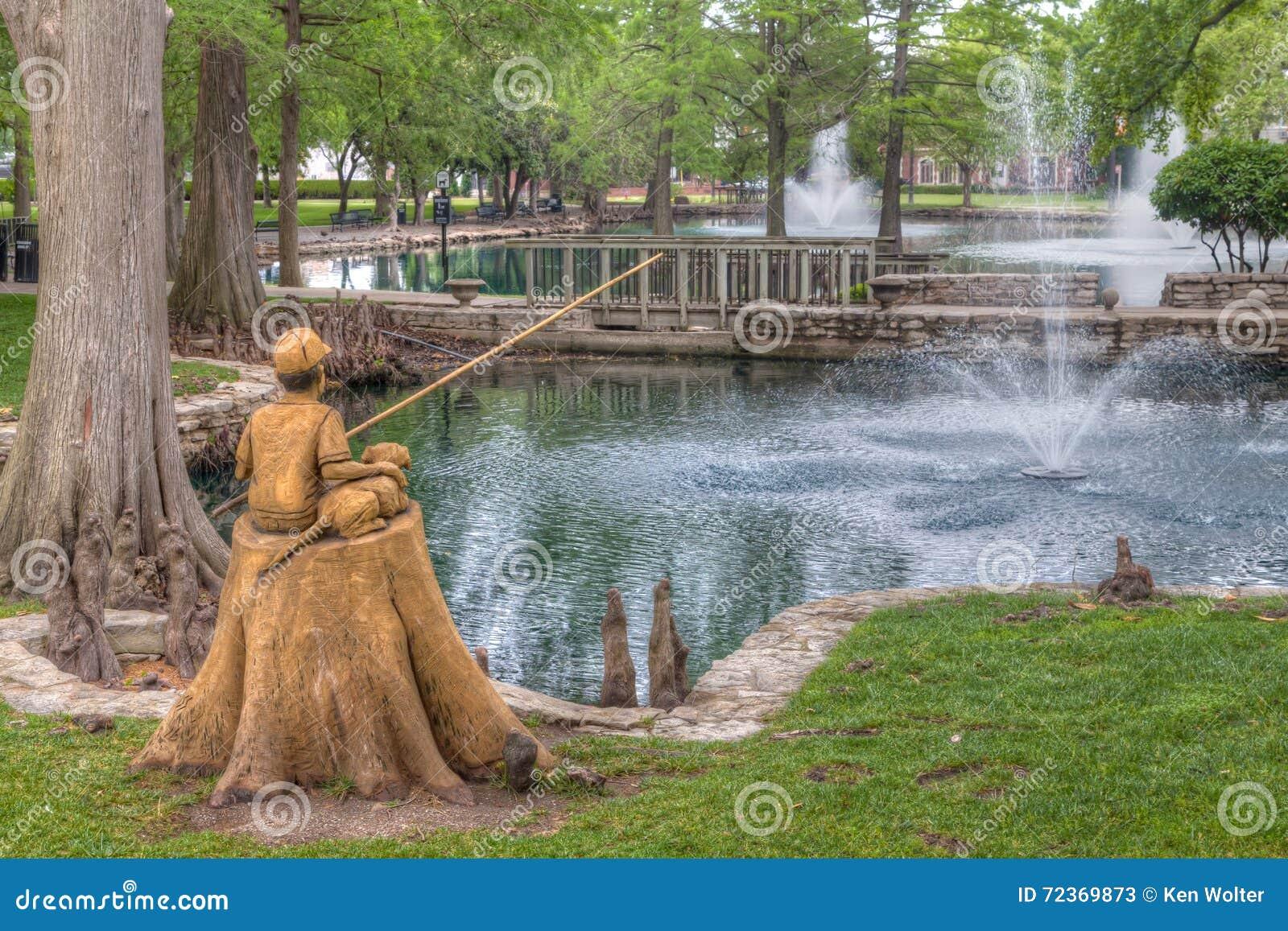 男孩和狗在希腊字母的第八字池塘的渔雕塑