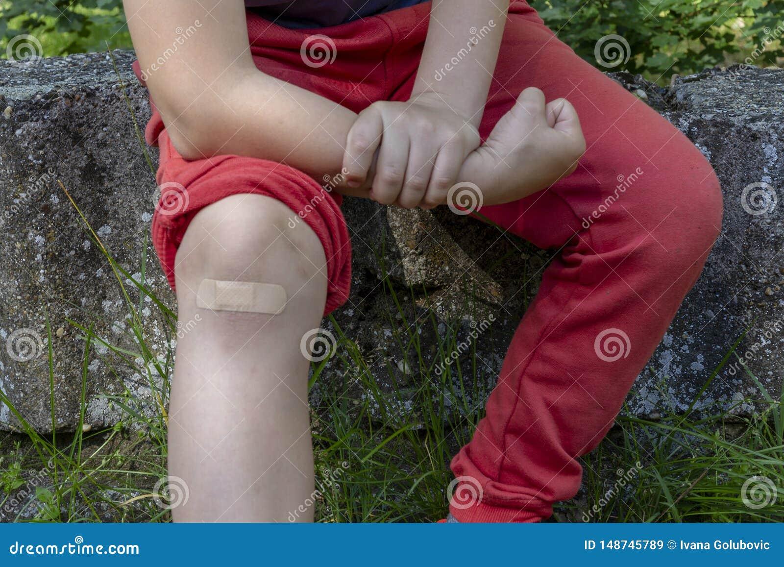 男孩在与绷带的痛苦中在他的膝盖