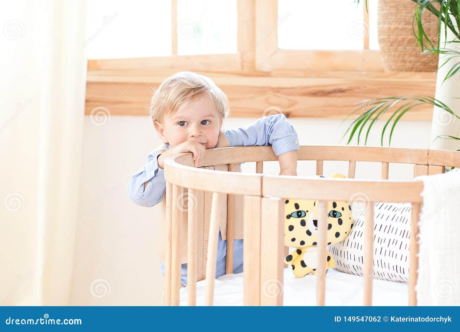 男孩在托儿所站立单独在一个轻便小床旁边 孤独的婴孩在幼儿园在小儿床附近 ?? 环境友好的孩子的